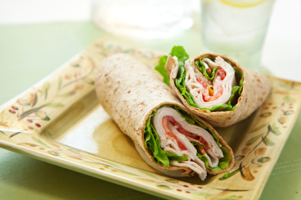healthy turkey wrap sandwich with lettuce, tomato, onion and peppers